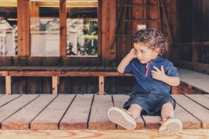 little boy sat on decking outside