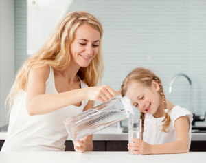 mother pouring glass of water for child