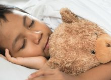 little boy in bed with teddy bear