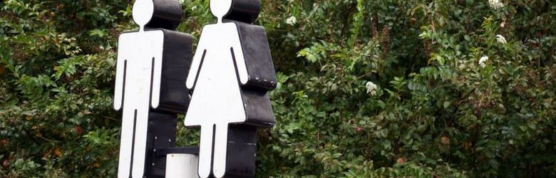 toilet sign in front of trees