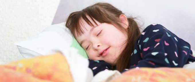 down's syndrome girl asleep in bed