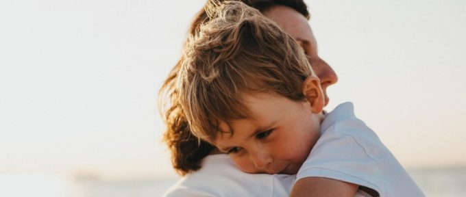 parent hugging young child and smiling