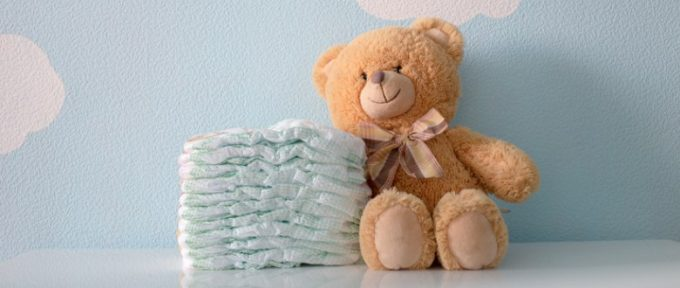 teddy bear beside pile of disposable nappies