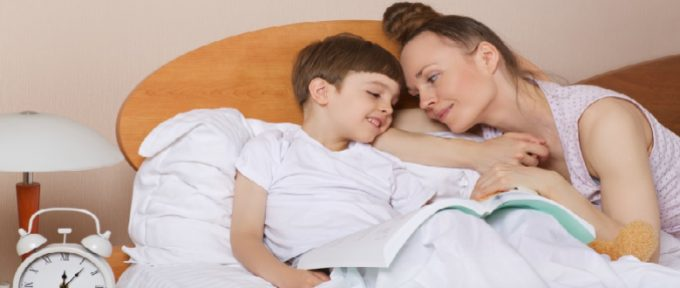 mother and son in bed with a book