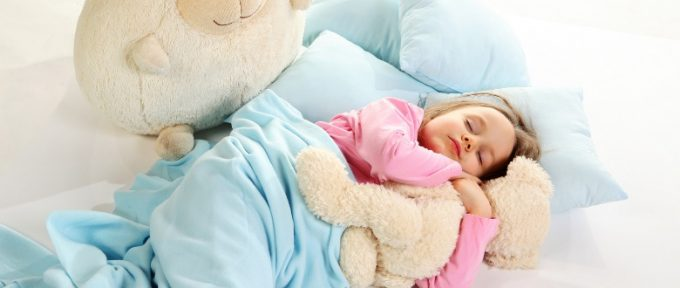 5 year old girl in bed with her cuddly soft toys