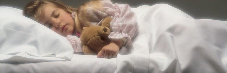 young girl asleep in bed with teddy bear