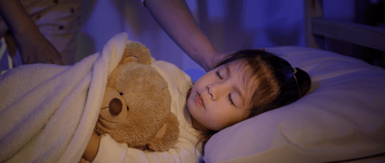 young girl asleep in bed with a teddy bear