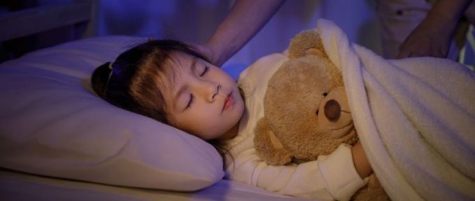 girl asleep with teddy bear
