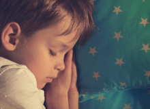 little boy asleep in bed with starry quilt