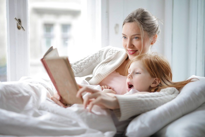 mother and daughter reading book in bed