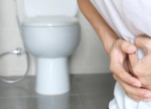 man constipated holding stomach near the toilet