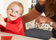 little boy with down syndrome smiling with his mum