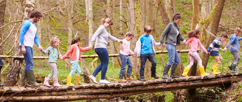 Group of Adults and Children walking along a tree
