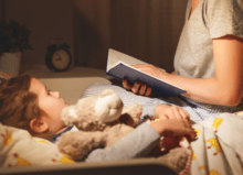 child in bed with mum reading a bed time story