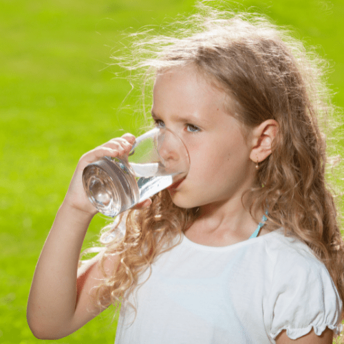 child drinking water from a glass