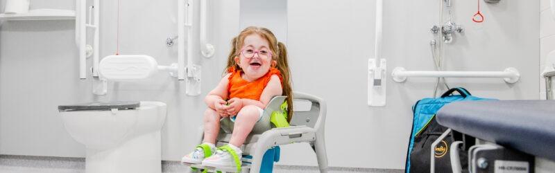 Girl using the Firefly GottaGo toilet seat