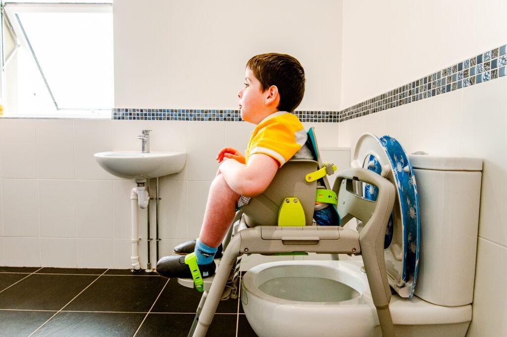 Boy using the Firefly GottaGo toilet seat